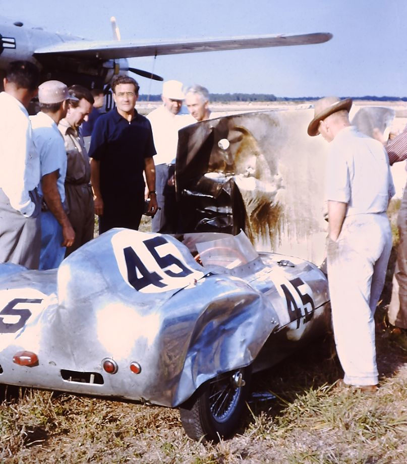 Briggs Cunningham (blue shirt), and several race fans, looking over the burned-out engine compartment of Lotus Mk. XI he was to take possession of after the race.  Colin Chapman is on his immediate right.