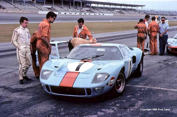 <strong>The John Wyer Automotive Ford GT40's on the pit road at Daytona.  Standing to the left is Jackie Oliver while Jacky Ickx sits in the driver's seat of the #1 GT.  To the right is the #2 GT.  That's David Hobbs putting on the blue helmet.  His co-driver was Mike Hailwood.  They were supposed to be the competition for Porsche.  Neither car finished.</strong>  (Photo credit: www.fredlewisphotos.com)