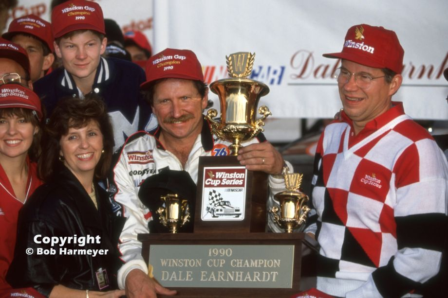 Dale Earnhardt celebrates his fourth NASCAR championship at Atlanta in 1990, while Dale Earnhardt, Jr.(upper left) looks at the trophy over his father's shoulder.