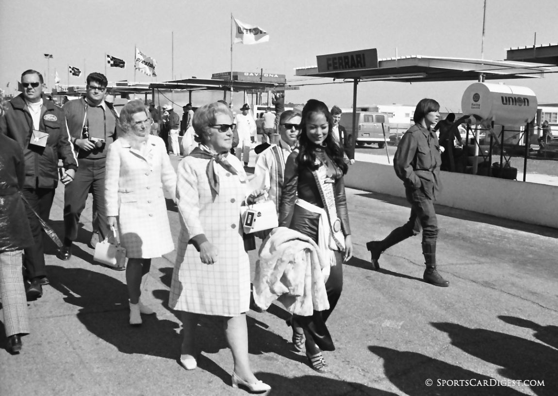 On race day Miss Universe, Gloria Diaz, and her chaperones walk the starting grid. The chaperones were very protective of Ms. Diaz and one look from them could freeze you in place if you got too friendly. (Lou Galanos photo)