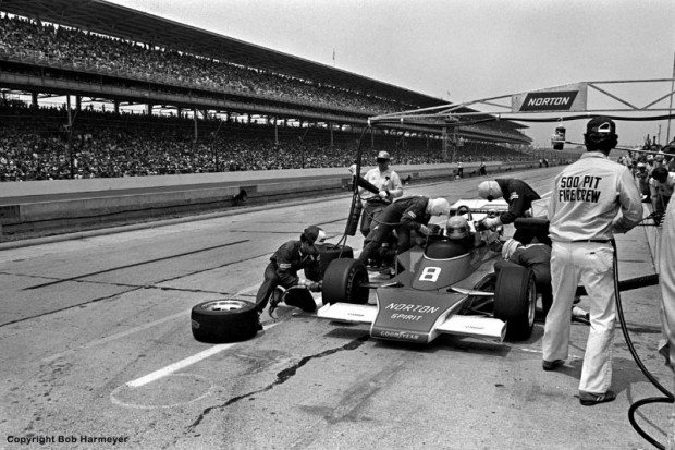 Tom Sneva makes a pit stop in Roger Penske's McLaren M24/Cosworth TC en route to a 2nd place finish in the 1977 Indianapolis 500. USAC regulations at the time allowed the overhead gantry assembly that carried air hoses to the right side of the car for the air jack and wheel guns.