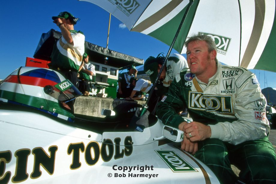 Paul Tracy (right) speaks with teammate Dario Franchitt (left, in car) before practice for the 1998 CART race in Rio de Janeiro, Brazil.