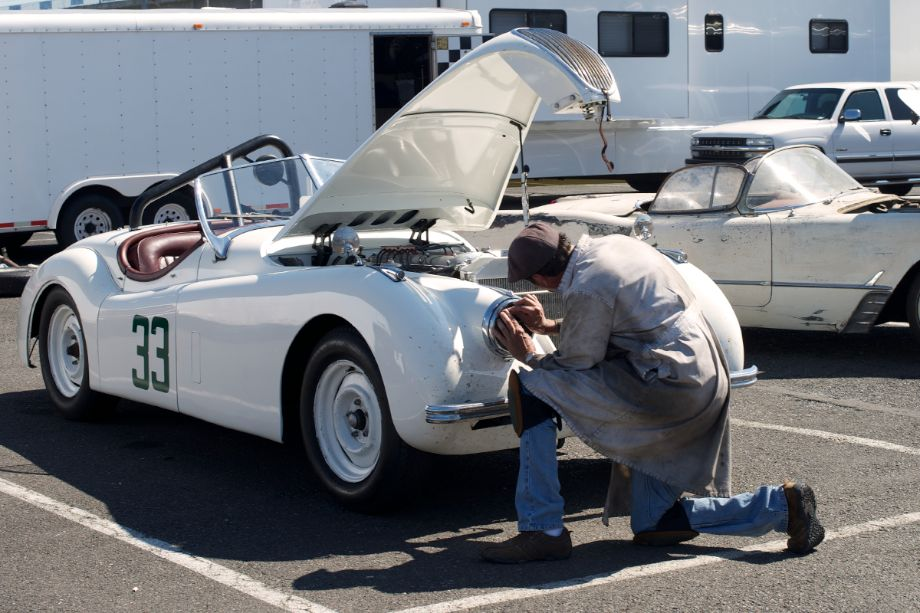 Jim Alder's XK120 Jaguar. Jim drove the Jaguar all the way from Reno raced for three days then drove it back to Reno. In between he replaced broken axel with a spare he just happened to have in the Jaguar's trunk. Here Jim is taping the headlights insuring he can use them on the drive home.
