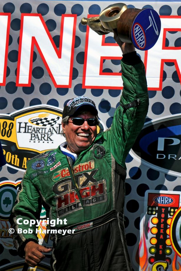 John Force celebrates with the NHRA trophy after winning the Funny Car class at Topeka in 2008. Force had been severely injured in a crash during the 2007 season and missed the remainder of the year. This victory at Topeka was his first since the accident.
