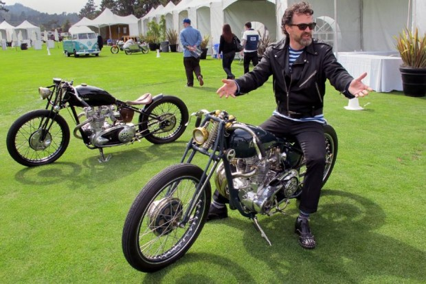 """Paul d'Orleans with the two previous Falcon Motorcycles that Ian Barry has designed and built.  Paul sits """"The Kestrel"""" that features a 1970 Triumph Bonneville motor that was cut in half and re-engineered by Falcon.  The other, with a 1950 Triumph Thunderbird engine, is """"The Bullet"""" created to reflect what a Triumph board-tracker might have looked like in time warp.  All three Falcons have been sold."""