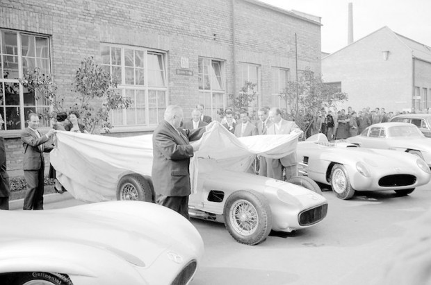 End of the 1955 motor racing season: Stirling Moss, Alfred Neubauer and Juan Manuel Fangio put the covers on the cars.