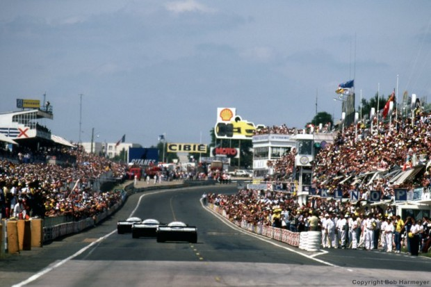 The winning Porsche 956 driven by Jacky Ickx and Derek Bell leads the other two Rothmans Porsche team cars past the pit lane near the finish.