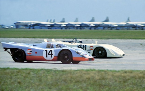 The #14 Porsche 917K of Jo Siffert, Leo Kinnunen and Brian Redman passing the #48 Porsche 908/02 of Steve McQueen and Peter Revson.  The photo was taken just at the beginning of the back airport straight and you can see the 917 powering up to pass the Steve McQueen car.  The 917 had so much power and torque that the body would lift up a couple of inches off the pavement going through the gears.  The Siffert Porsche was gridded second but failed to finish due to accident damage.  The McQueen car finished second by 23 seconds behind the Ferrari 512s of Mario Andretti.