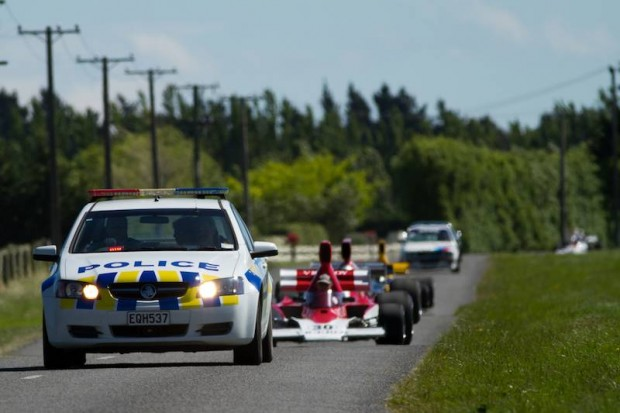 Under police escort six of the Formula 5000 single-seater racing cars rumble down Hasketts Road on their way to Templeton Primary School.