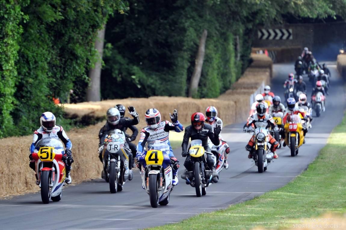 Wayne Gardner leads bikes down the Goodwood hill climb