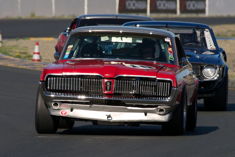 Jimmy Gallucci's 1967 Mercury Cougar leads a couple of Mustangs into turn ten.