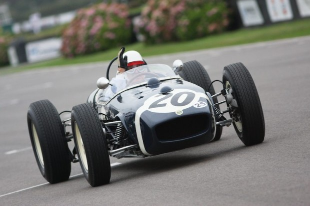 Sir Stirling Moss waves to crowd behind the wheel of the Lotus 18