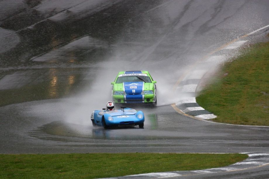 Doc Bundy in a 1964 Lotus 23B struggles with aquaplaning while leading eventual race winner Patrick Wilmot's 1984 Ford Mustang