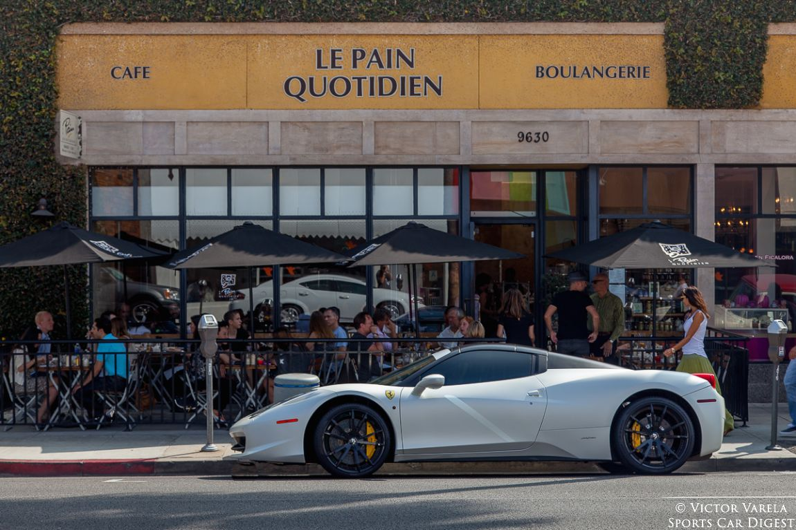 A Ferrari 458 Italia parked in front of a Beverly Hills Boulangerie.