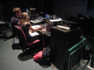 Students operate an audio console and projections during a community event in Hanaway Theatre