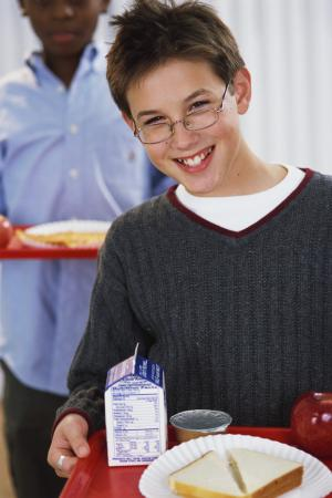 Photo of a young boy holding a lunch tray.