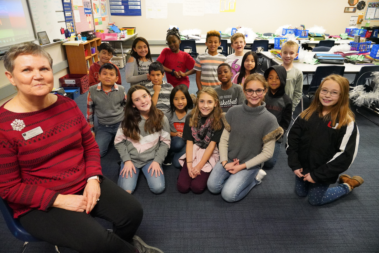 """Moore Elementary – Merry Lahti, 4th Grade Fourth grade teacher Merry Lahti has been named the 2019-2020 Teacher of the Year for Moore Elementary School. """"I think I have always been a teacher,"""" Lahti said.  """"I began by teaching my dolls and my younger brother and sister and went on to add neighborhood friends to the ;school' on our front porch.  I grew up in the in-between generation, before college was pretty much a given.  I would have been a perfect candidate to be the kind of teacher Laura Ingalls was – getting my credentials by passing a series of questions from a school superintendent.  Going to college could have been impossible except my grandmother passed away the week of my high school graduation.  My mother received a very small inheritance that basically paid for my first year at community college.  The rest was paid by student loans which by today's standards were quite small.  I thought it was the greatest thing in the world when I began my first job – teaching kindergarten – and getting paid to do it!"""" Lahti enjoys teaching most subjects.   """"Once upon a time I would have said math or social studies was my favorite. I still absolutely love teaching social studies,"""" she said.  """"I did not enjoy history as a student, either in high school or college, but as an adult, I discovered a love for the stories in history and remember vividly my first 'aha' of enjoyment.  I refuse to let history or geography be the boring subject I always thought it was. """"Six years ago I changed schools and stepped into teaching writing to four sections of fourth graders each day.  Before, I never would have said that I love, or even like teaching writing.  That, however, has changed.  I am able to give 50 to 55 minutes per class each day to my writers.  We have time to listen to books which can mentor us as writers and which can build our vocabularies.  My students hear my say 'I love words' over and over as we notice how words with similar parts also have related meanings.  We ha"""