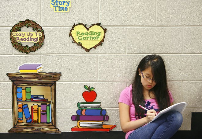 Phuong Quang reads in the library during a summer learning camp at Roy Clark Elementary School last week. The Union district school was named one of three model community schools in the country. MATT BARNARD/Tulsa World