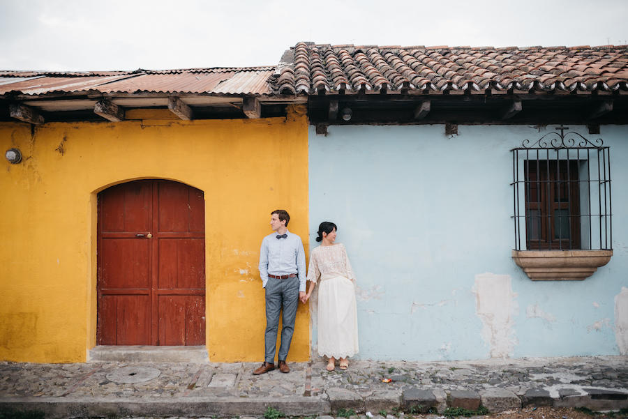 couple portraits in front of yellow and blue building