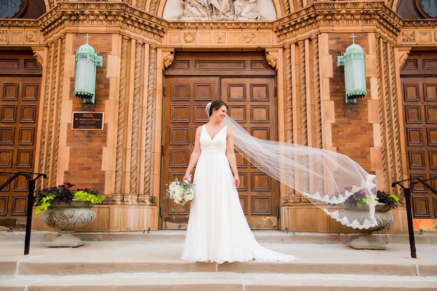 An outdoor bridal shoot with a light brown building behind the bride, who is holding her bouquet to her side and her veil is flowing in the wind on the opposite side.