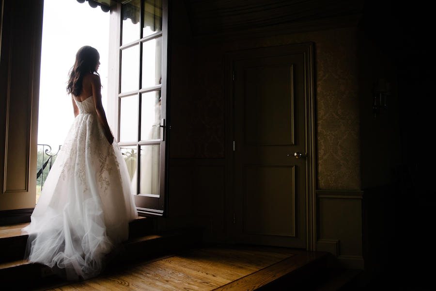 A wedding bridal portrait of the bride facing the door, her back to the camera and natural light coming in to highlight her and the details of her wedding dress.