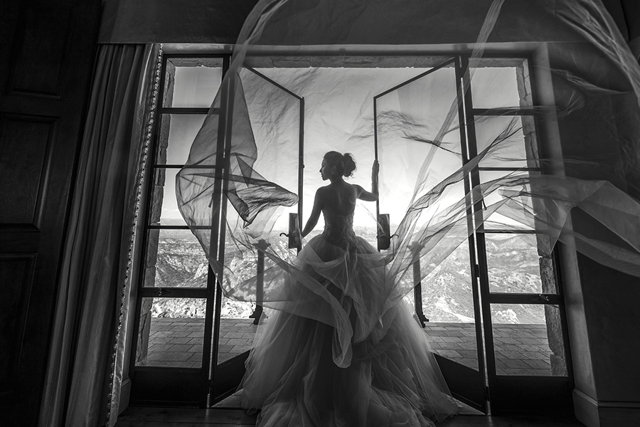 bride standing at the window with veil in the wind