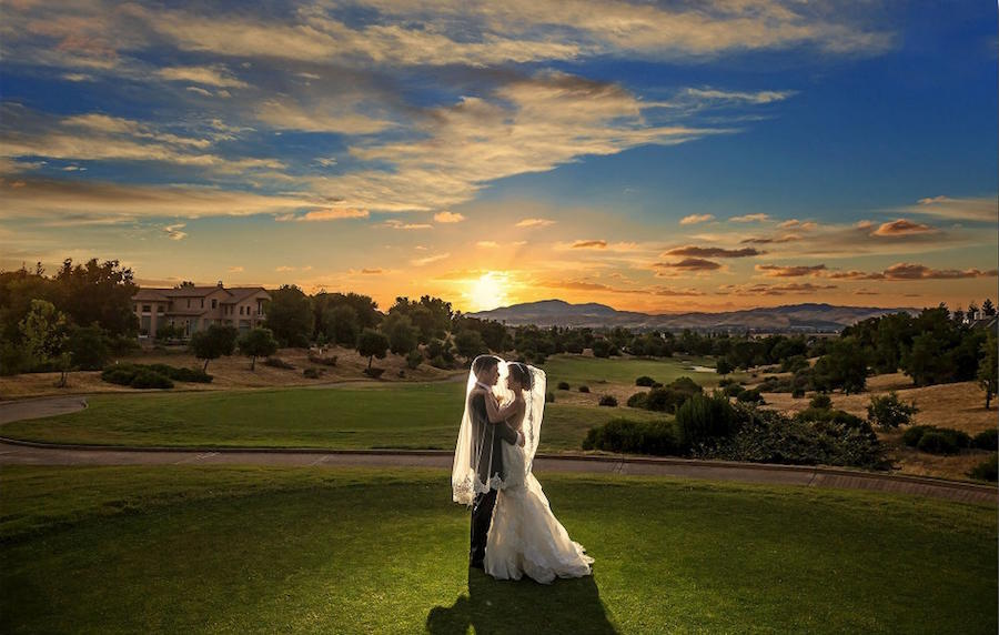A wedding photography shot of the bride and groom in an embrace under the bride's veil with the sun setting on a large landscape behind them.