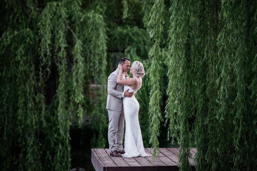A wedding photography image of the couple in an embrace standing on a dock with green hanging trees.