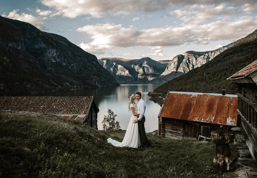 The bride is kissing the groom's cheek as they stand in the middle of two buildings and large mountains in the background.