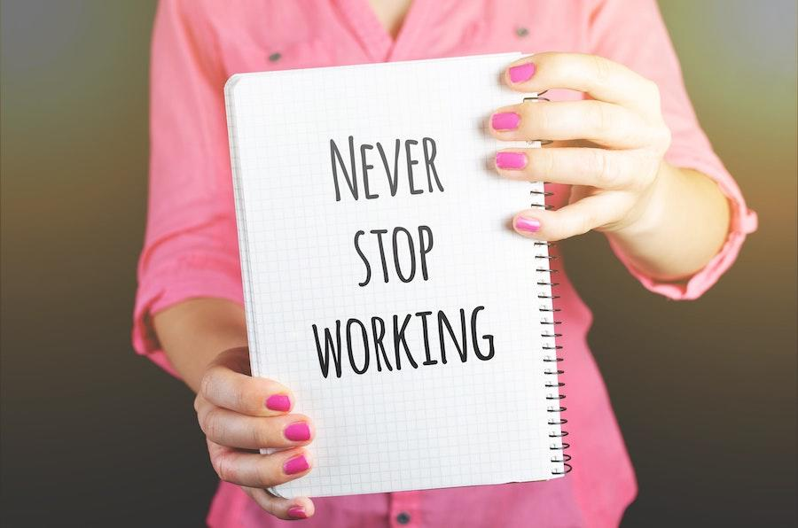 woman with pink nails and shirt holding a notebook that says never stop working