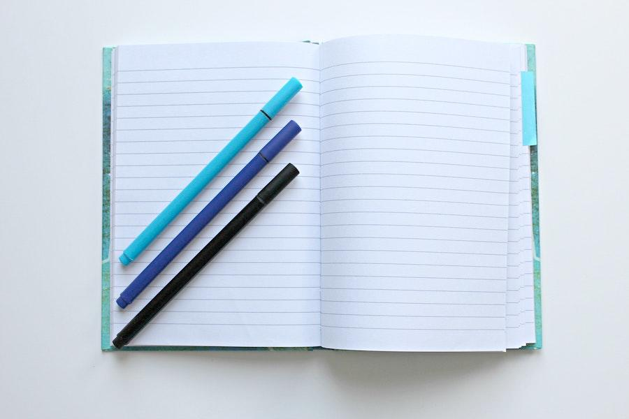 A notebook on a white surface with 3 pens, including 2 blue and one black.