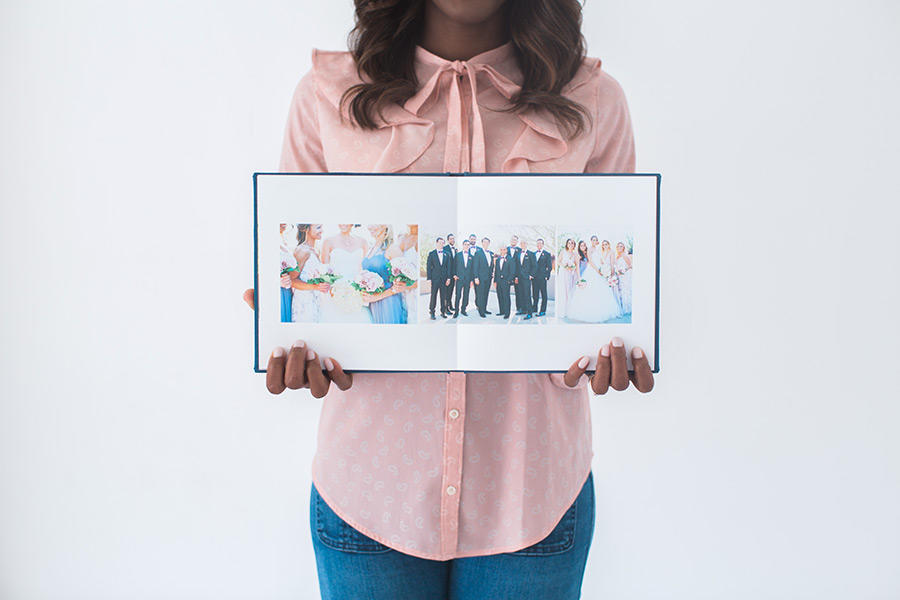 A woman with a pink blouse and blue jeans holding a wedding album spread open.