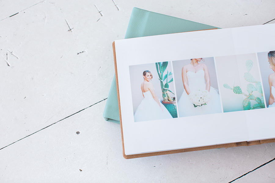 Two wedding photography albums on a white surface, with one of the albums open to a page with four images.