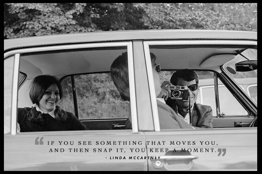 Photographer Linda Mccartney's inspirational quote on a black and white photo of a photographer from the side in the front seat, taking a photo of the passenger, while a woman with pig tails smiles in the backseat.