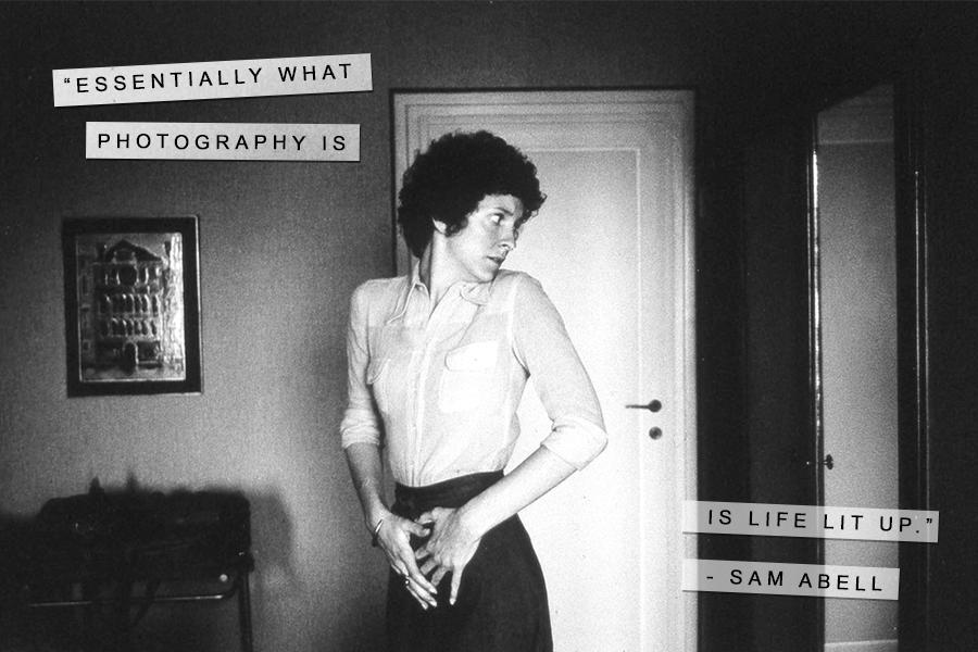 A Sam Abell photography quote with a black and white image of woman in a room looking back over her shoulder at a mirror.
