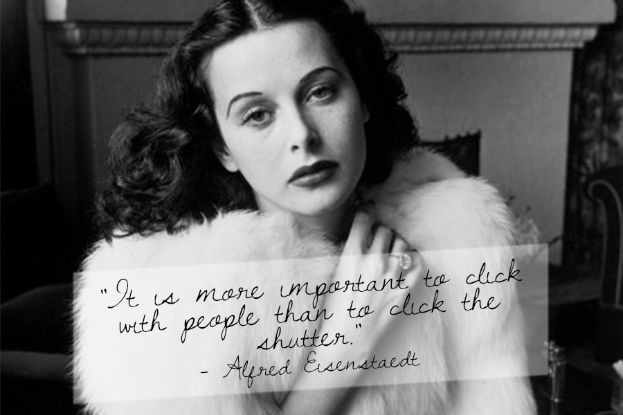 A top photography quote from Alfred Eisenstaedt with a black and white image of a woman holding her coat together at her neck.