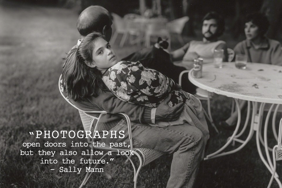 Sally Mann's photography quote over a black and white photo of four people at a table, with a girl sitting on her father's lap looking back at the camera, while the other people are not in focus.