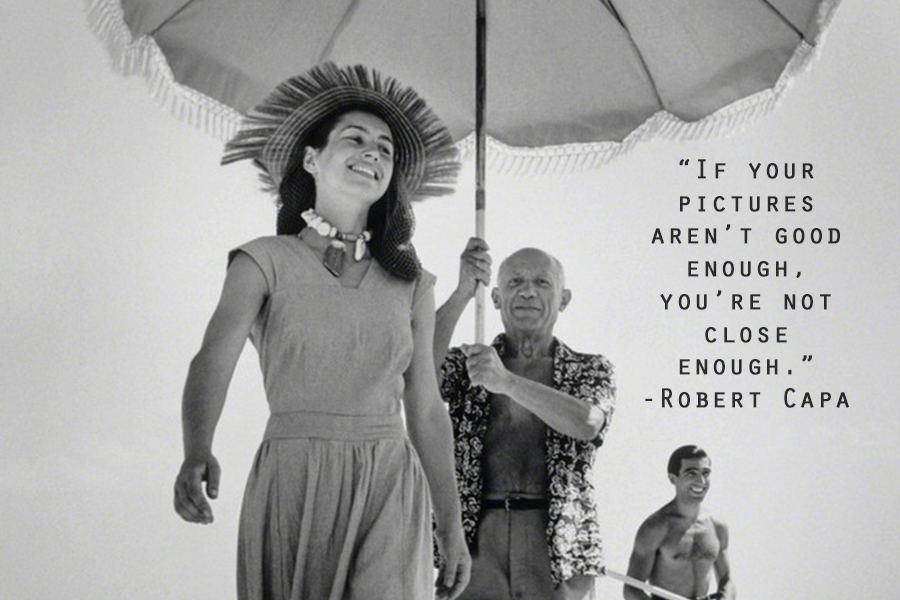 A Robert Capa quote about photography over a black and white image of a man holding an umbrella over a woman with a hat and shell necklace, while a shirtless man smiles in the background.