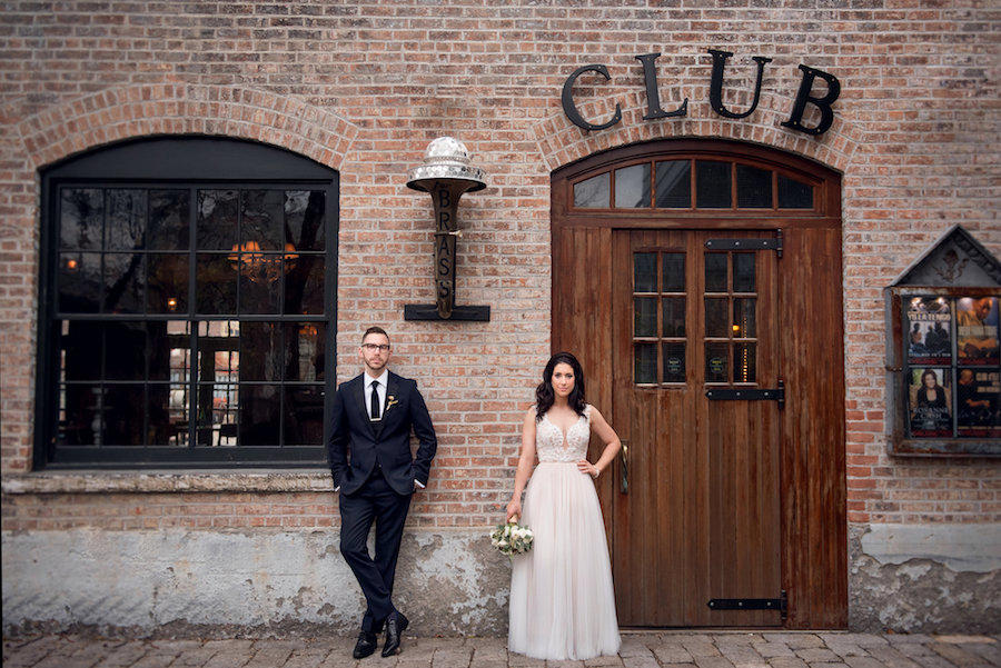 bride and groom outside a brick building