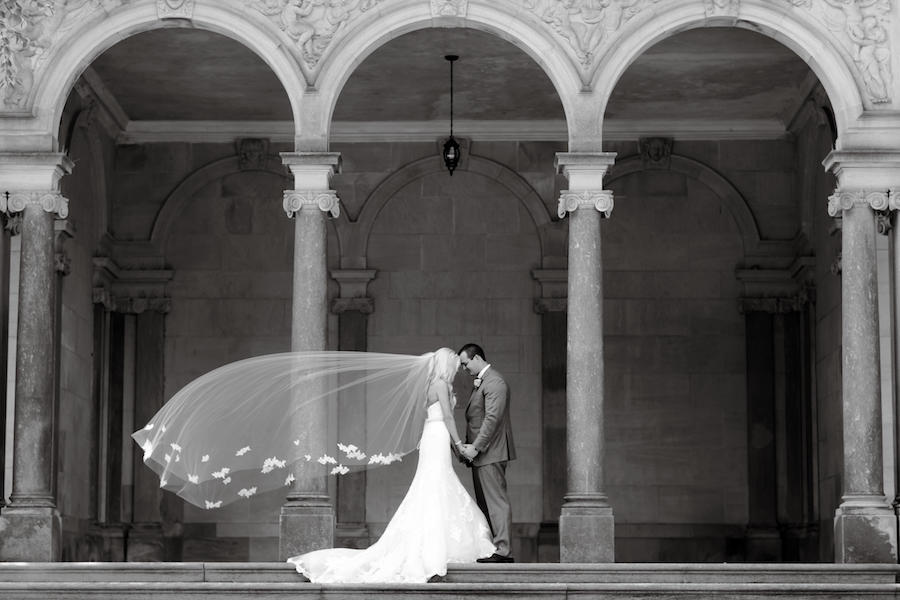 A black and white photo of a bride and groom outdoors, with the bride's veil flowing in the wind.