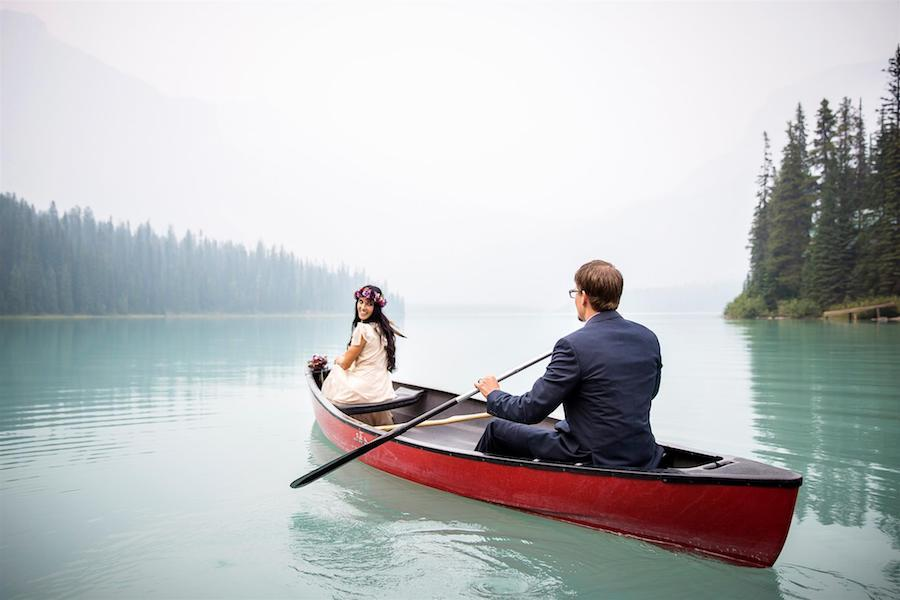 A wedding image of a couple in a canoe on a lake, with the groom holding the oar and the bride looking back at him.