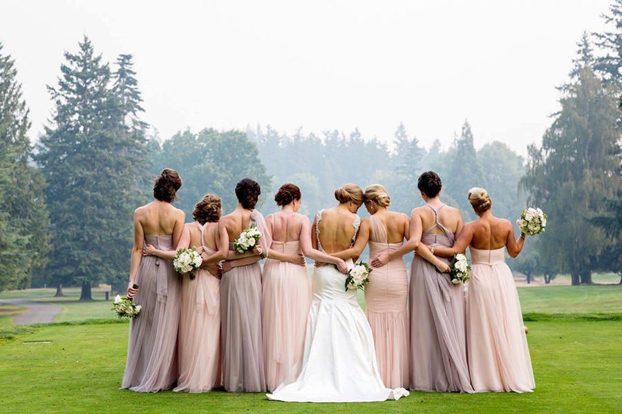 An outdoor wedding photography image of the bridal party, locked arm-in-arm, with their backs turned to the camera.