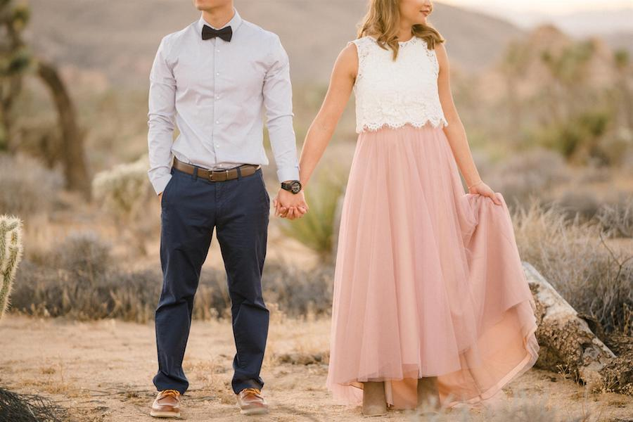 A couple holding hands during their engagement shoot, the bride wearing a white top and pink long skirt, and the groom wearing a button-up, a bowtie, and blue pants; their faces are cut off so the focus is on their bodies and hand holding.