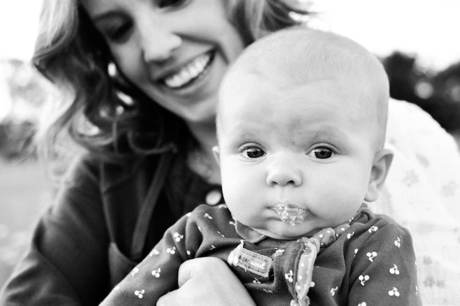 A black and white image of Leeann Marie, Wedding Photographers with her daughter in her arms.