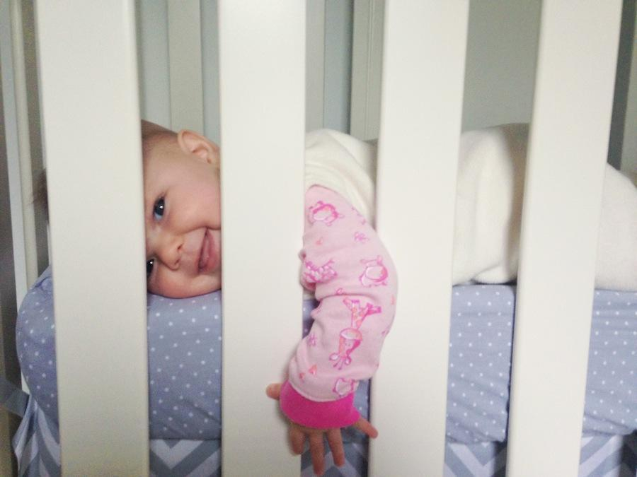 An image by Leeann Marie, Wedding Photographers of her daughter laying in her crib and facing the camera.