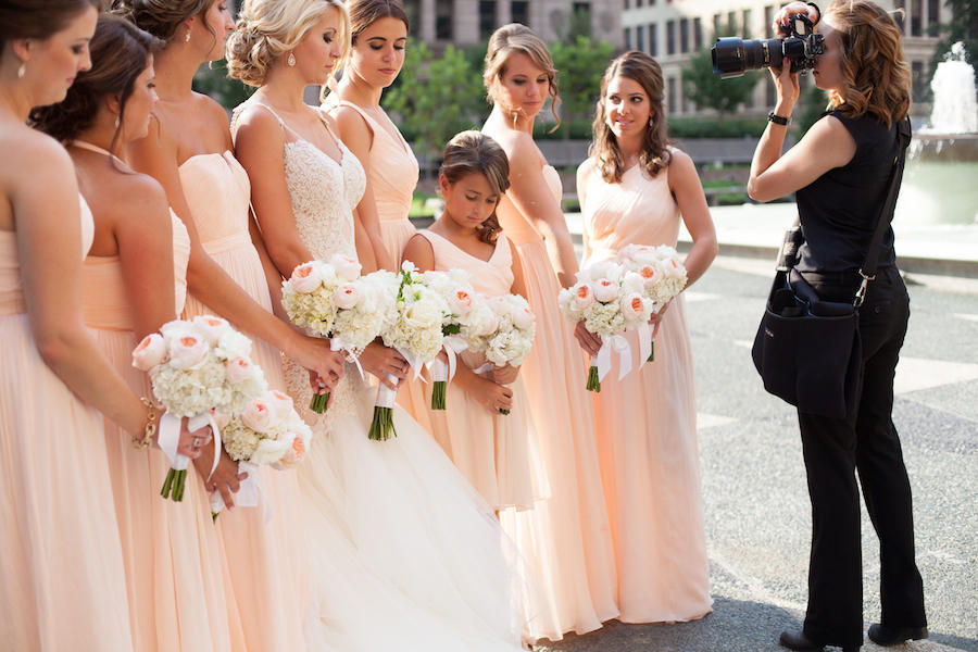 A behind-the-scenes photo of Leeann Marie, Wedding Photographers as she takes photos of the wedding bridal party outdoors.