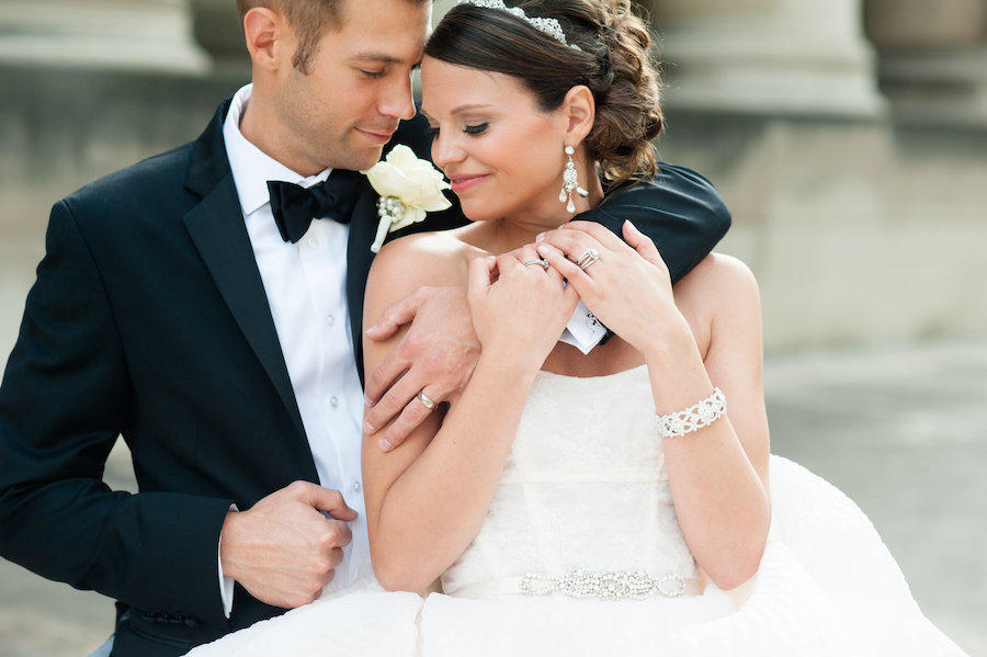 A wedding couple portrait of the bride and groom, with his arm wrapped around her and their heads leaning on one another.