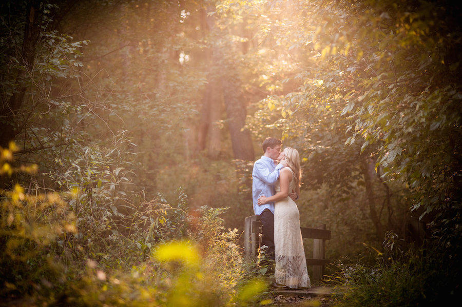 An outdoor engagement session with sunlight shining through the trees on the couple facing one another and kissing.
