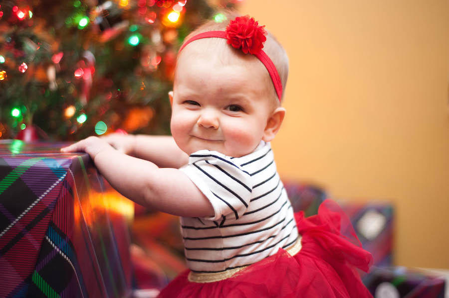 An image by Leeann Marie, Wedding Photographers of her daughter holding a present with a Christmas tree blurred in the background.