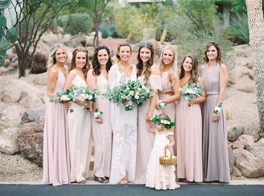 An image of the bridal party outdoors holding their bouquets, with the flower girl in the front.